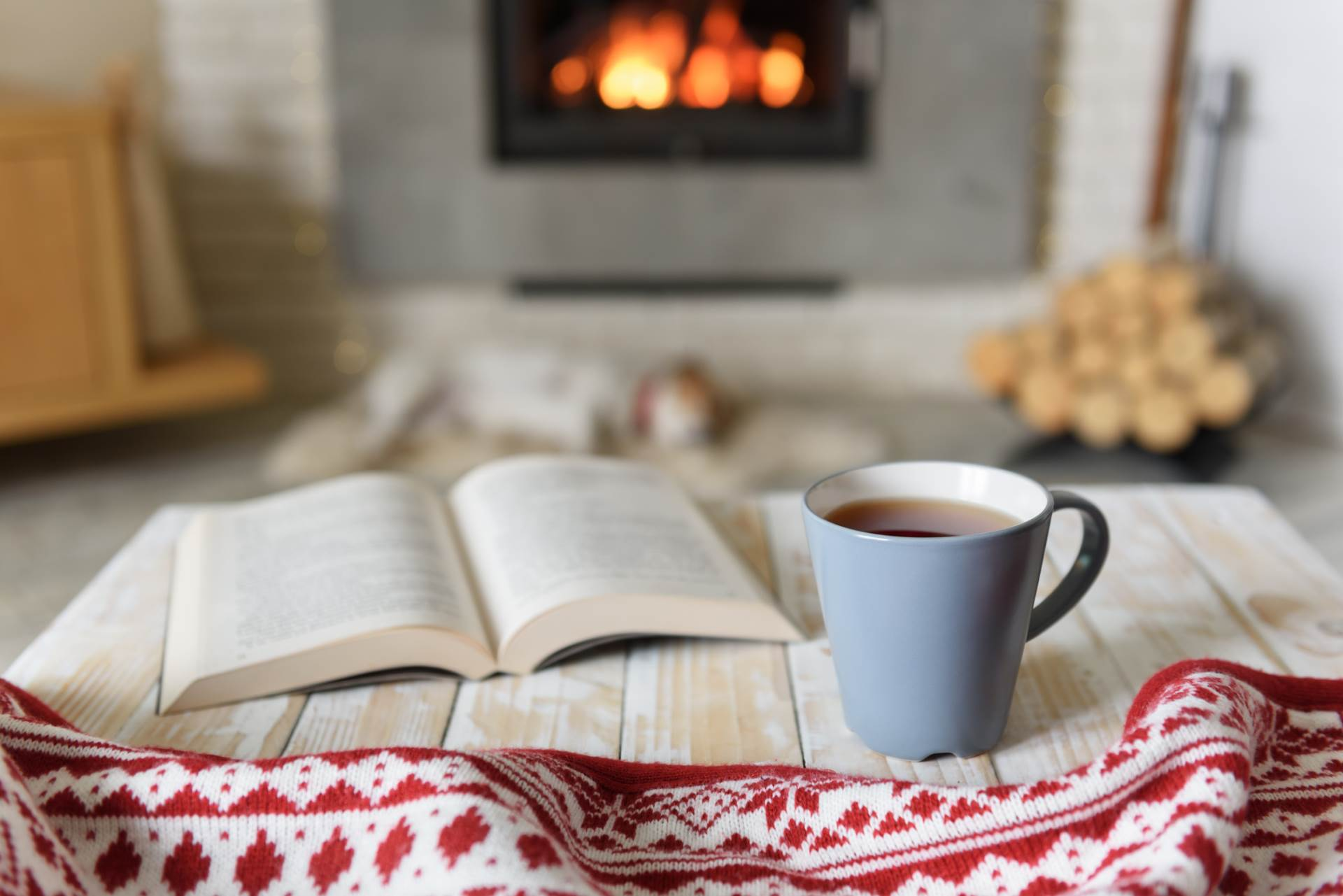 Book and cup of tea near burning fireplace. Hygge concept