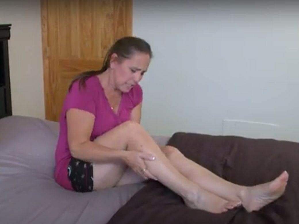 Žena sedi na krevetu ima grčeve u nogama